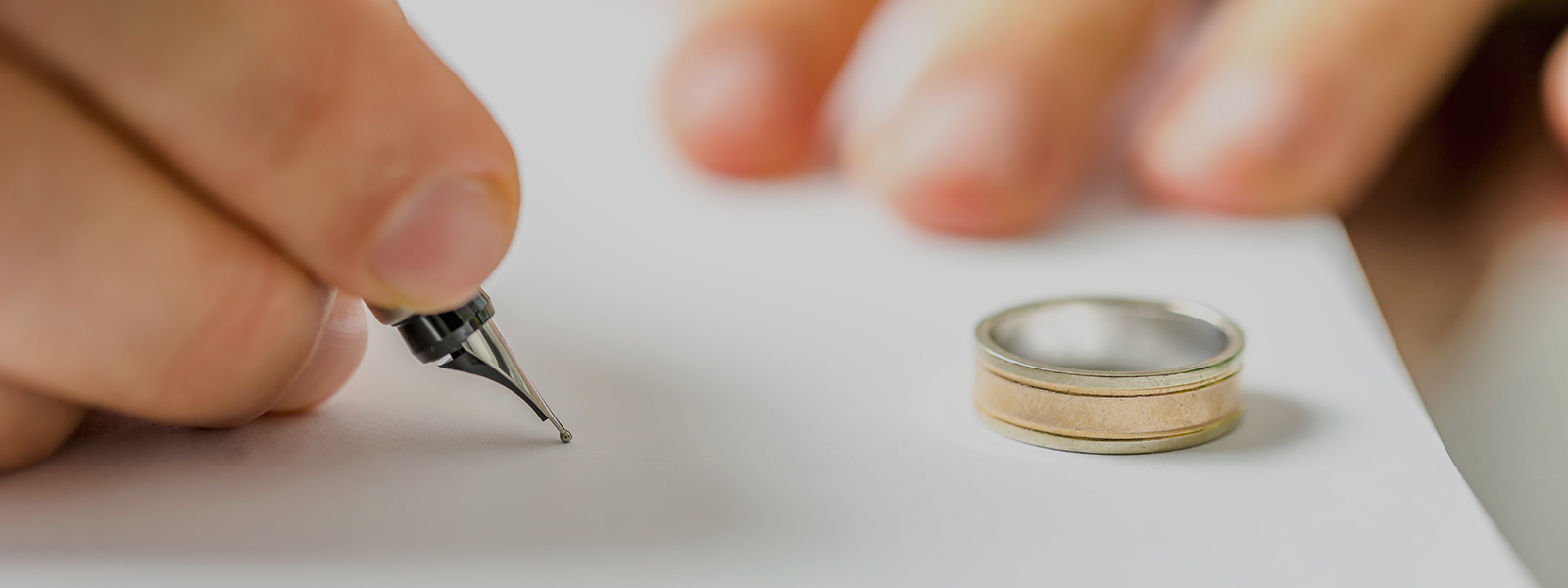 Closeup of male hand signing divorce papers - absolute divorce